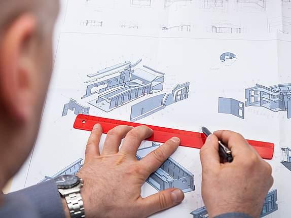 Entwickler von Daetwyler Industries misst eine technische Zeichnung aus