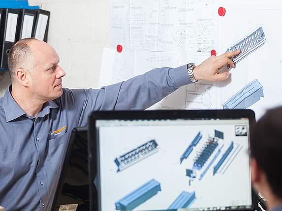 Projektleiter von Daetwyler Industries zeigt auf Maschinenbauteil in der Entwicklung